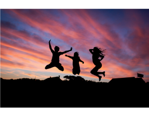 People leaping in front of sunset